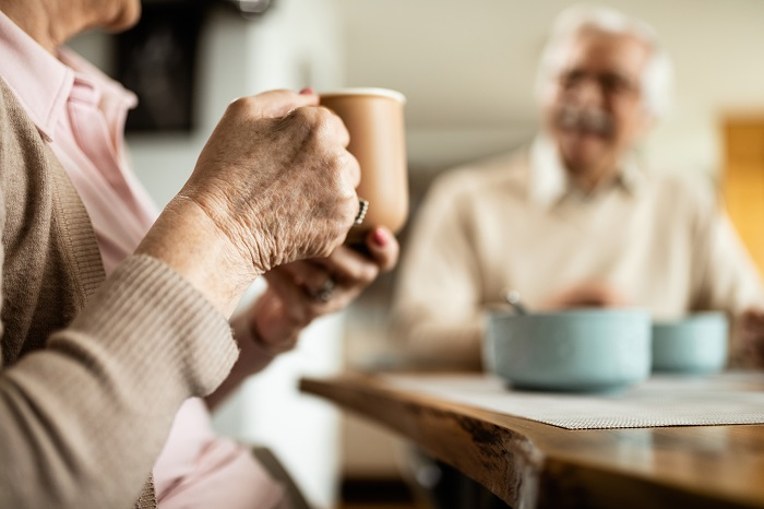 Senior woman holding coffee cup at breakfast table