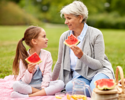 Senior woman with her granddaughter on a picnic eating watermelon to keep hydrated