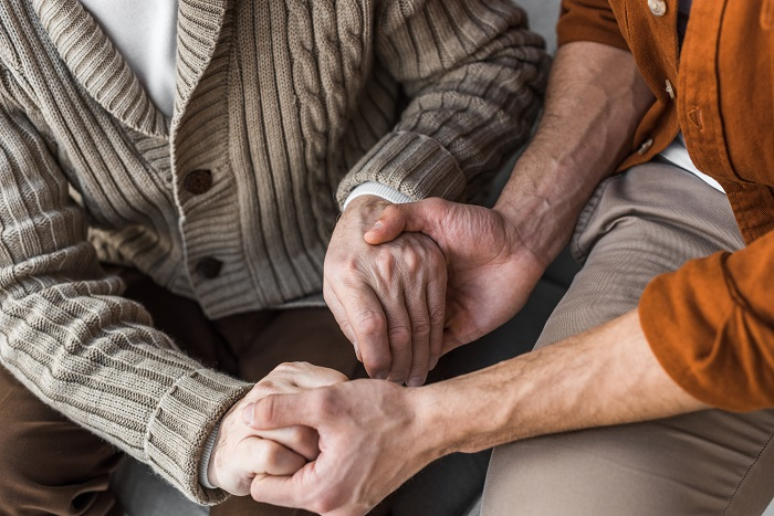 Father with dementia holds son's hands