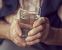 Senior holding a glass of water