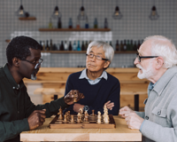 three senior friends playing a game of chess together