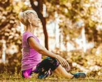 senior woman sitting on a fitness matt outdoors stretching.
