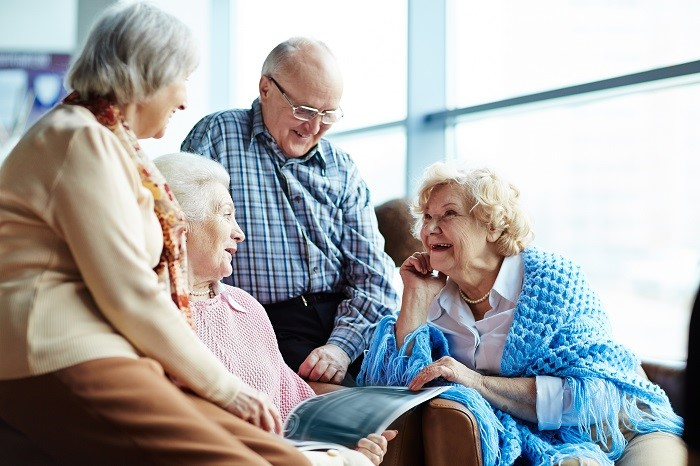 Group of seniors talks together and looks at magazine
