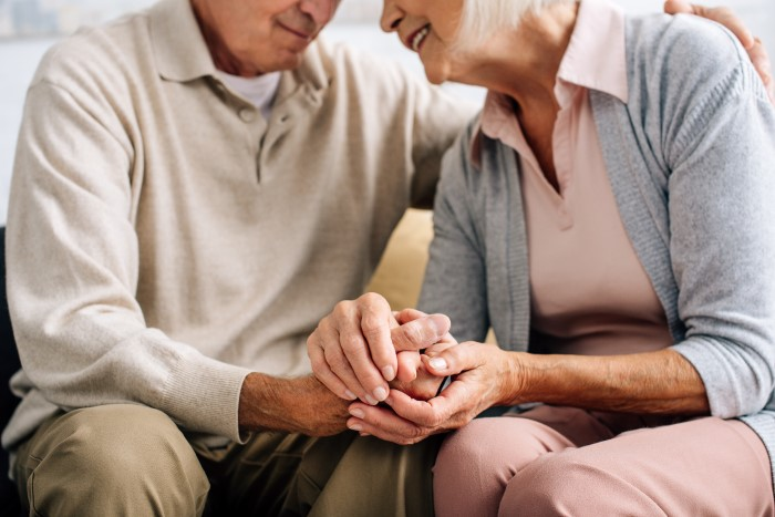 Senior couple sit and practice breathing exercises