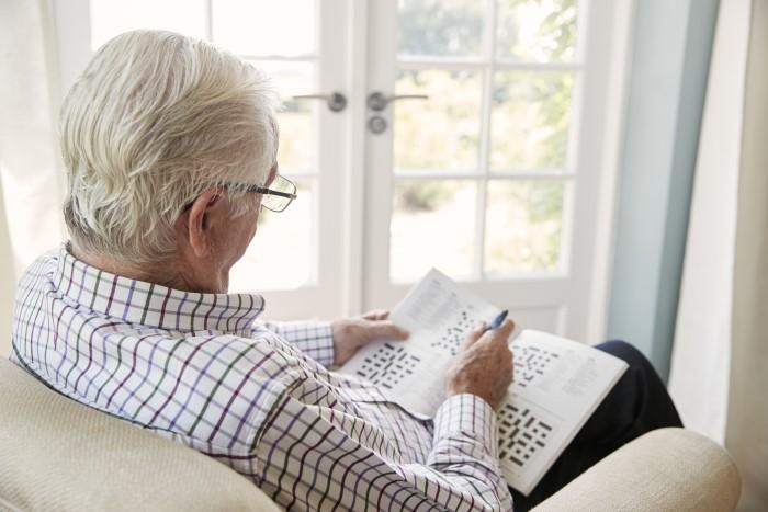Senior man does crossword puzzle