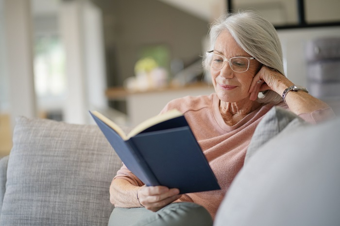 Senior woman reads book at home during COVID-19 quarantine