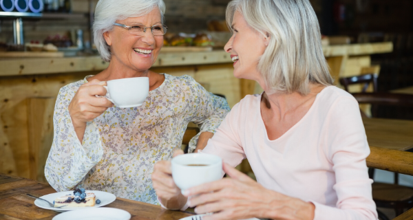 Older adult women friends meet over coffee