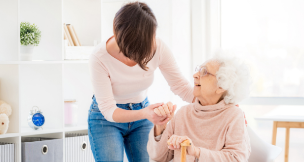 Adult child helping elderly mother with a cane to stand up.