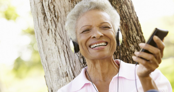 Mature woman listens to podcast on caregiving on her mobile phone