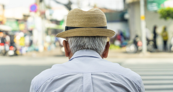 Senior man with Alzheimer's disease from behind wearing a hat sitting on a bench in New York