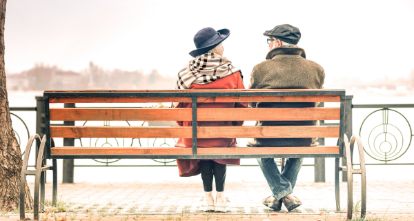 Senior couple sitting on a park bench discussing memory care on long island
