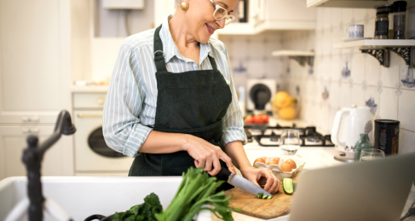 senior woman standing at kitchen counter, cutting cucumber for healthy meal included in the MIND diet
