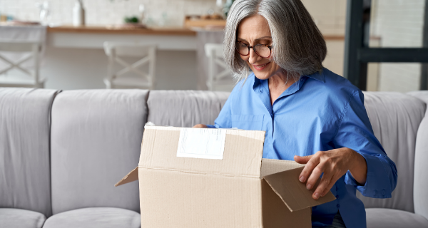 Senior woman packing a box for assisted living
