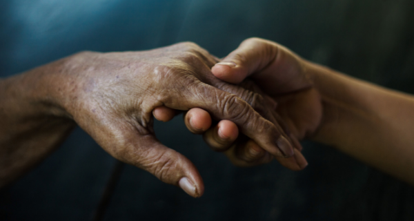 Caregiver holding the hand of an Alzheimer's or dementia patient.