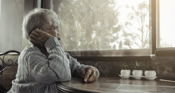 Senior with Alzheimer's confused and looking out the window.