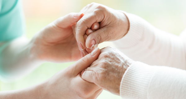 Loved one holding a senior woman's hands.