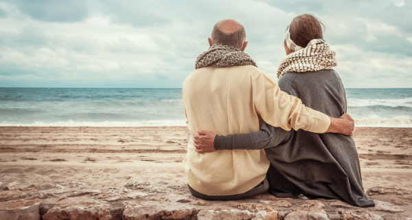 Senior couple with their arms around one another while sitting on a stone ledge and looking at the ocean.