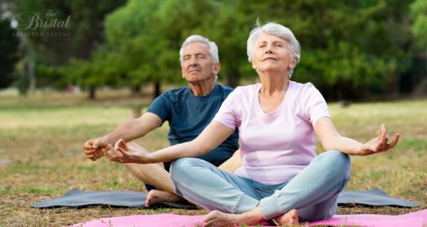 Senior couple meditating outdoors
