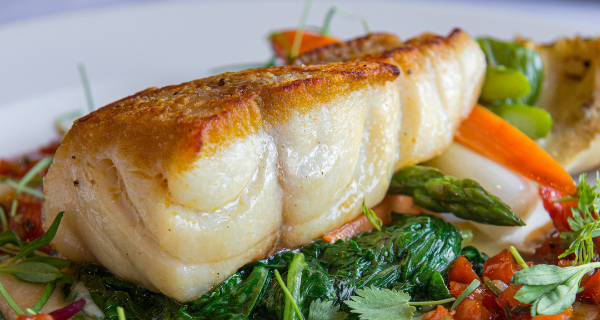 Pan-seared Florida grouper over a bed of vegetables.