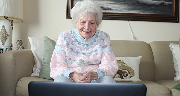 A resident at The Bristal smiles at computer screen