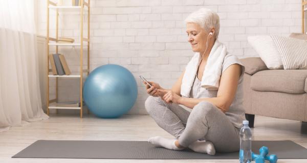 Senior woman exercises while reading senior lifestyle blog