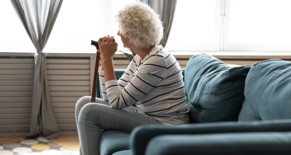 Senior woman sitting on her couch staring out the window