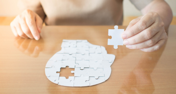 Woman holding puzzle piece to puzzle resembling a human head