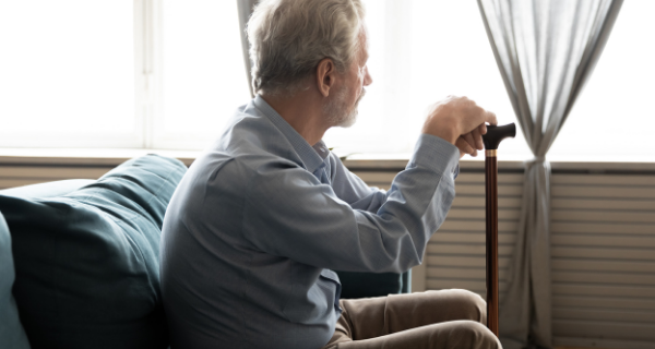Senior man with dementia fatigue looks out the window