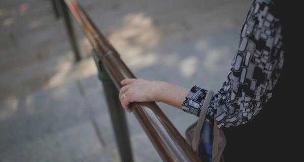 Women holding railing while walking down steps