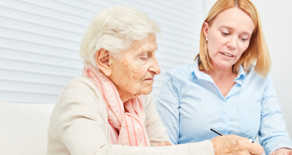 Female guardian helping senior woman complete paperwork