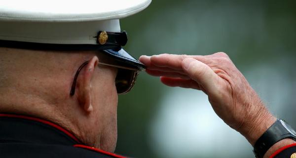 Senior male marine corps veteran salutes