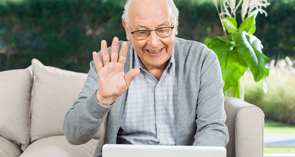 Senior man waving at his computer screen
